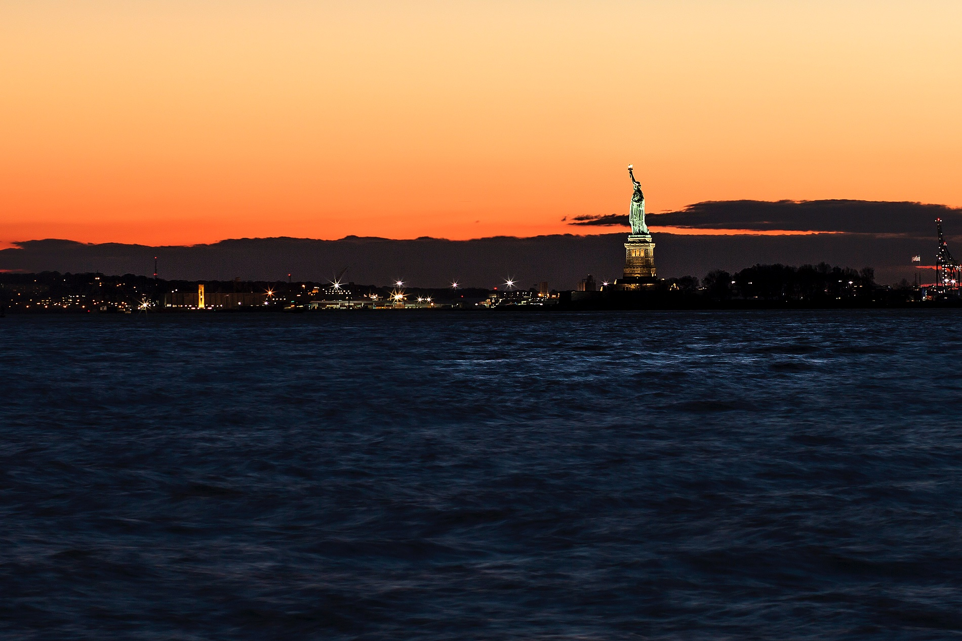 statue of liberty hudson river new york at sunset